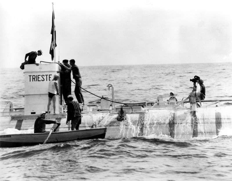 """The bathyscaphe Trieste, displaying the Italian and Swiss flags, is shown after its record plunge of 3,150 meters, 10,330 feet, to the bottom of the Thyrrhenian Sea off the island of Ponza, about 50 miles west of Naples, Sept. 30, 1953. Jacques Piccard holds onto his father, physicist Auguste Piccard, holding on to the turret, before descending into a rowing boat. Jacques Piccard, one of the last great explorers of the 20th century passed away on Saturday, Nov. 1, 2008 at his home on the edge of Lake Geneva in Switzerland, the Swiss SolarImpulse project said in a press release and on its Website on Saturday. He was 86. In 1960 Piccard and his companion Don Welsh dived deeper than any man before. With the bathyscaphe """"Triest"""" they reached a depth of almost 11'000 meters bellow sea level. (AP Photo/File)"""