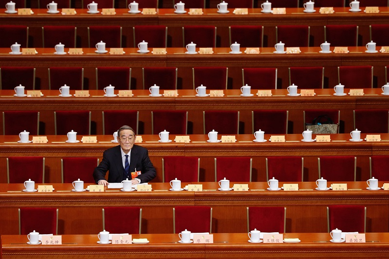 This picture taken on March 3, 2013 shows Chinese economist Li Yining taking his seat on the opening session of the Chinese People's Political Consultative Conference (CPPCC) at the Great Hall of the People in Beijing. Thousands of delegates from across China meet this week to seal a power transfer to new leaders whose first months running the Communist Party have pumped up expectations with a deluge of propaganda.  CHINA OUT     AFP PHOTO