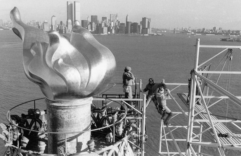 Operai rimuovono l'impalcatura dalla fiaccola della Statua della libertà durante i lavori di restauro al monumento, durati dal 1984 al 1986. La foto è del 17 dicembre del 1985 e sullo sfondo si vede lo skyline di Manhattan, con le Torri Gemelle.  (PAUL DEMARIA/AFP/Getty Images)