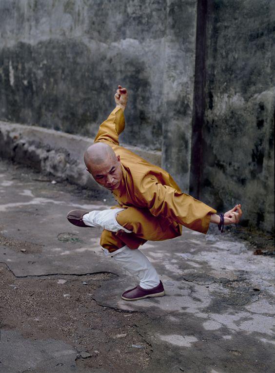 01381_11; Shaolin Monastery; Hunan Province; China; 08/2004; CHINA-10121NF. A man balances himself. Retouched_Ashley Crabill 06/11/2013