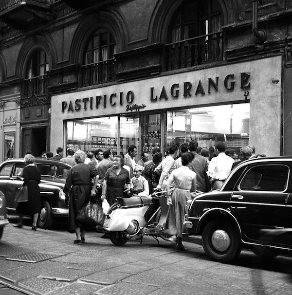 Il pastificio Lagrange, aperto nel 1872 dal cuoco Domenico Toso, ora diventato pastificio De Filippis, a Torino, 23 luglio 1956. Davanti all'entrata del negozio c'è il ciclista torinese Nino Defilippis, figlio dei proprietari, insieme a un gruppo di tifosi: quel giorno aveva appena vinto una tappa del Tour de France. (©Silvio Durante/Lapresse)